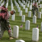 Members of the 3rd U.S. Infantry Regiment, 'The Old Guard,' place flags at grave sites during the 'Flags-In' ceremony May 24, 2014 at Arlington National Cemetery in Arlington, Virginia. A small American flag was placed one foot in front of more than 220,000 graves in the cemetery to mark the Memorial Day. (Photo : Mark Wilson/Getty Images)